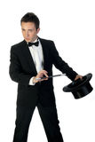 Magician with wand and hat. Young handsome magician holding his hat and magic wand during show isolated on white Stock Photo