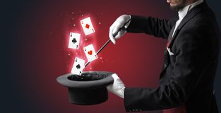 Magician making trick with wand and playing cards. Magician with white gloves conjuring playing cards from a cylinder with magic wand stock images