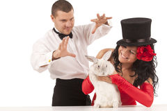 Magicians with  bunny. Closeup portrait of cute magicians with  bunny against white background Royalty Free Stock Images