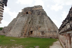 The Magicians Pyramid Uxmal Yucatan Mexico. A mayan stone temple facade with columns, a square and the imposing stone magicians pyramid Royalty Free Stock Image