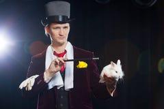 Magicien avec le lapin, homme de jongleur, personne drôle, magie noire, illusion sur un fond noir photographie stock libre de droits