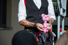 Magicien créant un ours rose hors d'un ballon à une partie d'enfants images libres de droits