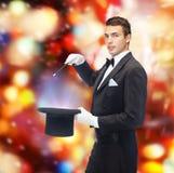 Magicien dans le chapeau supérieur avec le tour magique d'apparence de baguette magique Images stock