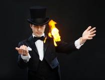 Magicien dans le tour d'apparence de chapeau supérieur avec le feu Photo libre de droits