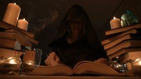 Magicienne en gros plan moyenne de fille dans un capot dans une chambre noire lueur d'une bougie et en recherchant un charme reto banque de vidéos