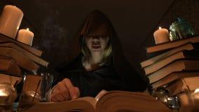 Magicienne en gros plan moyenne de fille dans un capot dans une chambre noire lueur d'une bougie et en recherchant un charme reto clips vidéos