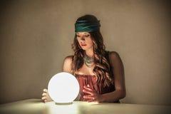 Magiczna kobieta patrzeje kryształową kulę Obrazy Royalty Free
