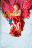 Magiczny dziecka lying on the beach w czerwieni, błękitny tło Zdjęcie Royalty Free
