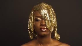 Magiczny surrealistyczny złoty amerykanin afrykańskiego pochodzenia kobiety model z jaskrawym błyskotliwości makeup i glansowaną  zbiory wideo