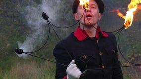 Magier brennt durch und legte das Feuer auf seinem Metallfan in einem Wald in der Zeitlupe nieder stock footage