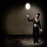 Magier, der einen glühenden Ballon hält Lizenzfreies Stockbild