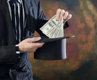 Magier, der Geld vom Spitzenhut zieht Lizenzfreies Stockbild