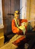 Magier mit der schönen orange Kleidung, die einen Levitationstrick tut stockfotografie