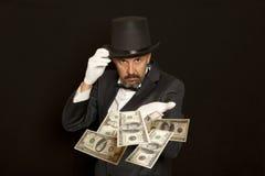 Magiershow mit Dollarbanknote Lokalisiert auf Schwarzem Stockfotos