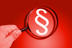Maginfier with paragraph sign. Hand with magnifier and paragraph sign on red background royalty free stock photos