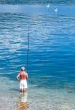 Magiore Lake. Arona, Italy - May 23, 2012: A senior fishermen in white knickers on the Maggiore lake royalty free stock photo