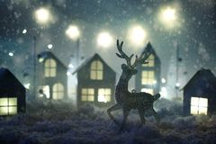 Magisch Kerstmisdocument dorp De winter achtergrondlandschap met huizen, bomen, herten op ijzige blauwe achtergrond royalty-vrije stock foto's