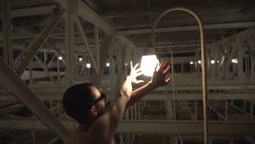 Magisch van licht De naakte mens in zonnebril bewondert gloeilampen stock footage