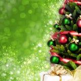 Magisch verzierter Weihnachtsbaum mit Bällen, Bändern und goldenen Girlanden auf einem unscharfen grünen glänzenden Hintergrund Stockbild