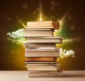 Magische boeken met straal van magische lichten en kleurrijke wolken Stock Afbeeldingen