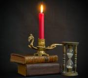 Magische boekenzandloper en kaars stock foto's