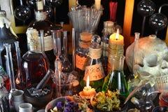 Magische flessen en brandende kaarsen op heksenlijst Stock Afbeeldingen