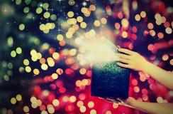 Magische Geschenkbox mit Lichtern in ihren Händen Stockbilder