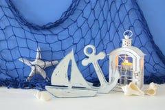 Magische Laterne mit Kerzenlicht und hölzernem Boot im Regal Verrostete, alte, symbolische Kette von einem Anker mit Booten verbl Stockfoto