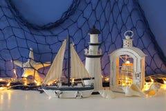 Magische Laterne mit Kerzenlicht und hölzernem Boot im Regal Verrostete, alte, symbolische Kette von einem Anker mit Booten verbl Lizenzfreie Stockfotos