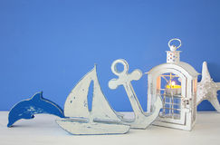 Magische Laterne mit Kerzenlicht und hölzernem Boot im Regal Verrostete, alte, symbolische Kette von einem Anker mit Booten verbl Lizenzfreies Stockfoto