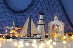 Magische Laterne mit Kerzenlicht und hölzernem Boot im Regal Verrostete, alte, symbolische Kette von einem Anker mit Booten verbl Lizenzfreie Stockfotografie