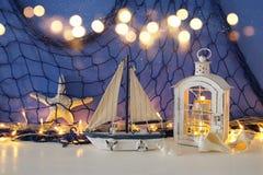 Magische Laterne mit Kerzenlicht und hölzernem Boot im Regal Verrostete, alte, symbolische Kette von einem Anker mit Booten verbl Stockbilder