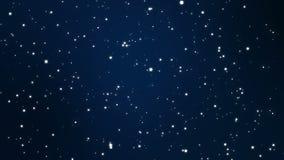 Magische sparkly Partikel, die auf einem Hintergrund des blauen Schwarzen flackern
