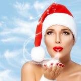 Magische Weihnachtsfrau in Santa Hat Blowing Sparkling Stardust Lizenzfreies Stockfoto
