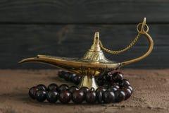 Magischer Aladdin Lamp mit Gebetsperlen auf brauner Tabelle stockfotografie
