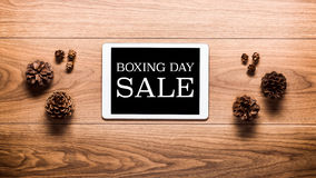 Magischer 26. Dezember-Verkaufsthemahintergrund, Kiefernkegel und digitale Tablette Lizenzfreies Stockfoto