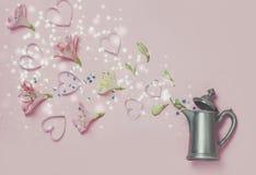 Magischer Frühlingsauftritt von Blumen und von Herzen vom Weinlesekessel auf rosa Hintergrund Draufsicht, flache Lage romantische Stockbild