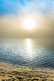 Magischer Morgen auf einem Strand mit einem Schleier des Nebels über einem See Stockfoto