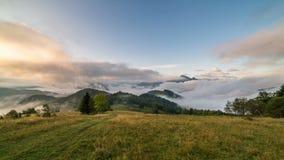 Magischer nebeliger Morgen mit den Wolken, die über schöner Landschaft bei Sonnenaufgang in den Herbstbergen rollen Zeitspanne ti stock footage