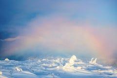 Magischer Regenbogen über dem Rasen und den schneebedeckten Bäumen hoch auf dem Berg lizenzfreies stockbild