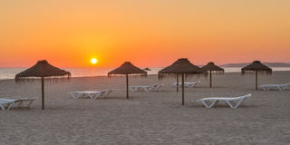 Magischer Sonnenuntergang am Strand Mit Sonnenruhesesseln und -sonnenschirmen für die Entspannung Lizenzfreie Stockfotografie