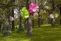 Magischer Wald mit künstlichen Blumen auf den Bäumen Stockbild