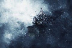 Magisches Bild Mysteriousand der alten Krone und des Buches über gotischem schwarzem Hintergrund mittelalterliches Zeitraumkonzep stockbild