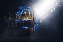 Magisches Bild Mysteriousand der alten Krone und des Buches über gotischem schwarzem Hintergrund mittelalterliches Zeitraumkonzep lizenzfreies stockfoto