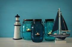 Magisches Weckgläser whith Kerzenlicht und hölzernes Boot im Regal Lizenzfreie Stockfotos