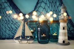 Magisches Weckgläser whith Kerzenlicht und hölzernes Boot im Regal Funkelnüberlagerung Lizenzfreie Stockbilder