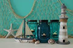 Magisches Weckgläser whith Kerzenlicht und hölzernes Boot im Regal Verrostete, alte, symbolische Kette von einem Anker mit Booten Lizenzfreie Stockfotografie