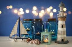 Magisches Weckgläser whith Kerzenlicht und hölzernes Boot im Regal Verrostete, alte, symbolische Kette von einem Anker mit Booten Lizenzfreie Stockbilder