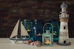Magisches Weckgläser whith Kerzenlicht und hölzernes Boot im Regal Verrostete, alte, symbolische Kette von einem Anker mit Booten Stockfotografie