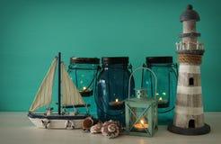 Magisches Weckgläser whith Kerzenlicht und hölzernes Boot im Regal Verrostete, alte, symbolische Kette von einem Anker mit Booten Stockbild
